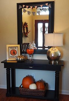 Pumpkins in a basket on bottom shelf of console table... Probably fake pumpkins.  Candy dish on top of table.