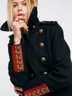 Cropped Wool Peacoat | In a wool-blend this classic style peacoat is in a cropped silhouette with bronzed metal etched buttons and lined hip pockets. Embroidery detailing on the back and sleeve cuffs and contrast red trim throughout. Lined.