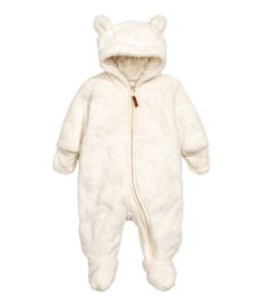 Natural white. Snuggle suit in soft pile with feet and mittens. Hood with attached ears, zip at front and along one leg, and openable, overlapping ribbing