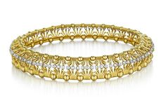 No, Not a Bracelet, It's a Choker by Jean Sclumberger for Tiffany. Designed as a highly flexible openwork choker, composed of a series of fluted links interspersed by polished gold spheres, accented by a line of circular-cut diamonds, mounted in 18K yellow gold, length 14 1/2 inches. Signed 'Tiffany & Co.' 'Sclumberger'.