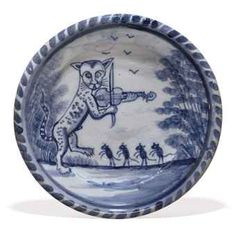 A LONDON DELFT BLUE AND WHITE DISH  CIRCA 1720-1740, LAMBETH  Painted with a cat standing on its hind legs playing a fiddle before four dancing mice, flanked by sponged trees, within a blue concentric band and dash border  13 5/8 in. (35.2 cm.) diameter