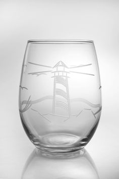 A stunning view of a large lighthouse in the distance is expertly engraved into these large stemless wine tumblers