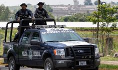 Officers' convoy was ambushed as it drove along a mountain road but prosecutors would not say if drug cartel Jalisco New Generation was behind the attack