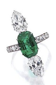 EMERALD AND DIAMOND RING, FRENCH, CIRCA 1920. Set with a cushion antique modified step-cut emerald weighing approximately 3.80 carats, bordered vertically by 2 pear-shaped diamonds weighing approximately 2.50 carats, the shoulders set with 8 old European-cut diamonds weighing approximately .40 carat, mounted in platinum, size 6 ½, French assay mark.