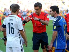 Referee Nicola Rizzoli (C) operates a coin toss in front of Philipp Lahm (L) of Germany and Lionel Messi (R) of Argentina prior to the 2014 FIFA World Cup Brazil Final match between Germany and Argentina at Maracana on July 13, 2014 in Rio de Janeiro, Brazil.