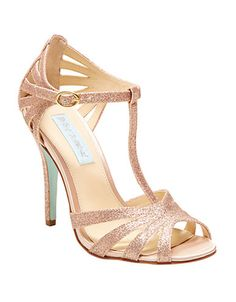 Shine with each step in these glittering T-strap sandals from Betsey Johnson. Featuring a glittered fabric upper, a rounded open toe, a buckle-adjustable ankle strap, allover cutouts and a covered heel.