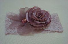 Faixa em renda com elastano na cor rosa chá com linda flor em cetim rosa e laço em fita organza e detalhe chaton. R$ 15,00