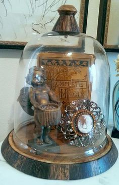 A triplet of three vintage items under a cloche.