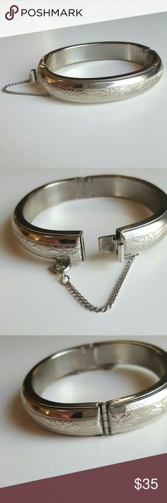 Vintage Flower Hinged Bracelet This lovely sterling silver bangle has lovely etched flower details with leaves in a band around the center. Hinged clasp with security chain. Perfect condition and  is 6.5 inched around the inside. Great with your favorite shirt and jeans. Other great accessories in my closet. Vintage Jewelry Bracelets