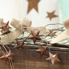 Rustic Garland with Burlap Bows and Rusty Tin Stars. Would love for above cabinets!