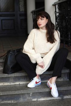 Laura wears a gunky sweater, black pants and Nike sneakers.