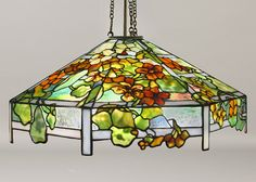 """Tiffany Studios """"Nasturtium"""" Chandelier  A Tiffany Studios New York glass and bronze """"Nasturtium"""" chandelier, featuring a leaded glass Favrile shade decorated with brilliant orange/red, orange/pink, yellow/orange and orange blossoms interspersed with green leaves on a cream trellis ground, hanging from a patinated bronze holder. Height is adjustable"""