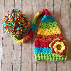 This super cute baby girl rainbow colored hat is made using 100% soft acrylic yarn. A multi-colored flower is attached. Perfect for newborn photos.