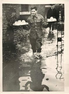 1939- British soldier takes tea to comrades working to repair banks of River Ravensbourne which flooded south London.