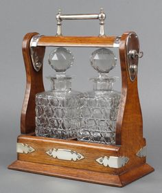 Lot 529, An Edwardian silver plated mounted oak 2 bottle tantalus with square cut decanters est £120-150