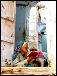 An old lady reads at her front door.