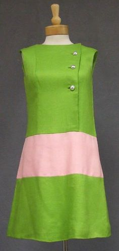 A wonderful 1960's Sarmi Day dress in a heavy lime and pink linen textured rayon. Sleeveless shift with three large silver toned button closures. Via Vintageous
