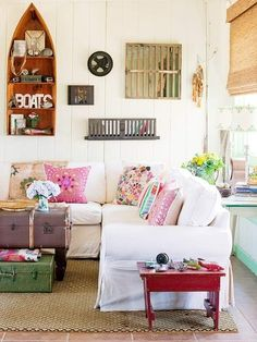 Pretty shabby chic living space in this lovely seaside cottage. Love the old trunks, boho cushions and fresh white walls and couch.