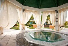 Dieser große Raum ist eine elegante und anspruchsvolle Pavillon mit einem privaten Whirlpool mitten im Zentrum. Die Vorhänge zwischen den Säulen sind große Dekoration, die dem Raum einen luftigen und entspannten Reiz geben.