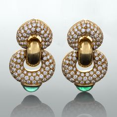 "Bulgari Diamond, Emerald and Gold Ear Pendants A pair of Italian 18 karat gold ear pendants with diamonds and emeralds by Bulgari. The earrings have 234 pavé round-cut diamonds with an approximate total weight of 5.50 carats, and 2 cabochon bezel set emeralds with an approximate total weight of 1.30 carats. From the""Doppio Cuore"" collection Bulgari first introduced in the late 1980's"