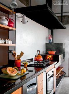 """Os acabamentos são simples, porém elegantes: a bancada da pia usa granito preto, e o piso, cimento queimado claro, feito na obra. """"Pela uniformidade, ele parece quase uma pedra"""", diz a arquiteta Christina de Castro Mello."""