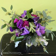Purple bridal bouquet of purple carnations, orchids, lisianthus, succulents and assorted greenery by Beautiful Blooms by Jen.