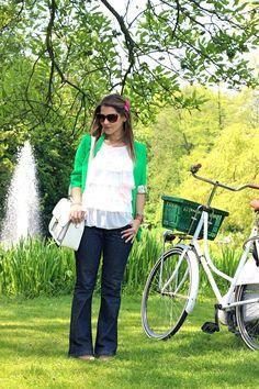 Catwalk Show: Linda, loira e japonesa: casaco verde e cordão de penas. Day look In Amsterdam. Retro bike.