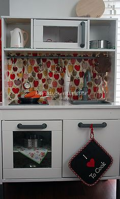 Lovely simple ikea play kitchen hack. Could match apron, tea towel and oven gloves to curtain fabric.