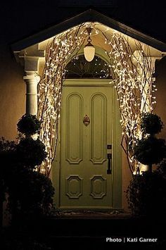 Using branches w/ lights by the front door for Christmas time - beautiful!