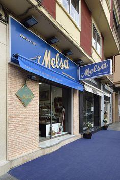 TIENDA MELSA. Proyecto integral de la nueva tienda de Embutidos Artesanos Melsa en Zaragoza. Estética tradicional y combinación de los colores colores blanco, azul y marrón que identifican a la marca.