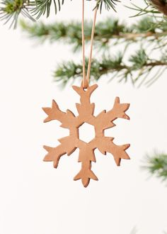 Handmade christmas ornament made as a snowflake in nature leather and wooden beads. Hight: 8,5 cm (without suspension), 16 cm (with suspension)