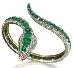 AN ANTIQUE EMERALD AND DIAMOND SNAKE BANGLE. Mid-19th Century. Photo via Christie's.