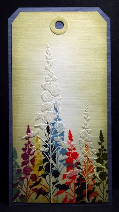 By Eileen. Sponge using a stencil & various colors using Distress ink on linen cardstock. Then use the same stencil with glossy Dimensional Paste & some Glamour Dust. Sponge edges of piece.