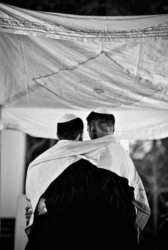 Jewish grooms at their Jewish wedding. Wrapping in tallit.