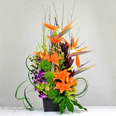 Zen artistry of ikebana styles with vibrant orange and purple colors delivered in a chic ceramic pottery, Includes birds of paradise and exotic orchids.