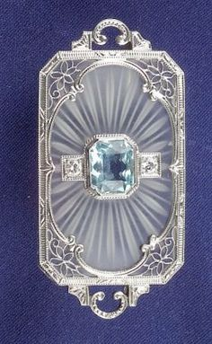 Art Deco 14kt White Gold, Aquamarine and Rock Crystal Brooch, bezel-set with a fancy-cut aquamarine flanked by box-set full-cut diamond accents on a shaped carved crystal plaque, openwork gallery, boxed.
