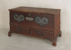 """Realized Price: $ 6518    Pennsylvania miniature painted poplar dower chest, dated 1802, decorated with two green sponged hearts on a red ground, 14 1/2"""" h., 24"""" w."""