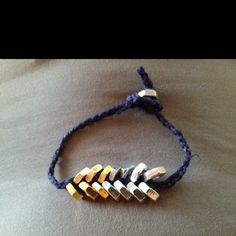 Navy blue chord with silver and brass hex nuts braided in.