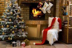 Christmas room with fireplace, chair, and a few presents under a decorated fir tree