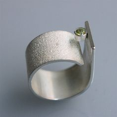 Contemporary minimalist handmade ring for him and her! This ring is made of sterling silver and has a 3mm peridot. It is very confortable to wear and you also can easy change the size a little bit so it suits in winter as in summer perfectly. The ringsize is 54(eu) but I can