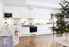 Kiiltävän valkoinen keittiö on Parman A la Carte -mallistosta. Välitilassa on lasinen taustalevy. Tasot ovat komposiittia. Aada kurkkaa sisäleikkimökistä. Jouluvaloilla koristeltu pahvitalo on ostettu Lidlistä.