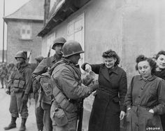 """GIs of the 79th Infantry Division getting some """"refreshments"""" from French civilians."""