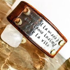 This is a custom cut, dyed, hand stamped and hand tooled leather cuff.  The metal face has brass rivets and silver tone plate.  This is a love gift for a couple, they actually had matching ones made to say this loving saying in Italian.