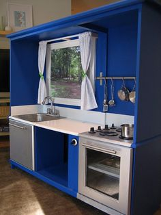 Made from an old entertainment center?   I've seen a lot of play kitchens, but this is one of the sharpest I've seen! I love that they actually made the appliances stainless steel! I think I know a few little girls who would love this.
