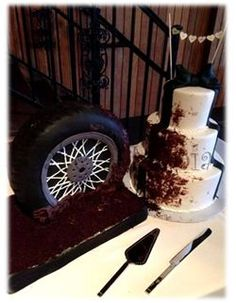 Grooms cake destroys chic wedding cake. Edible tire cake and 3 tier wedding cake covered in edible mud!! FUN! www.cake-a-mania.com or FB/cakeamania