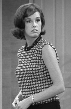 Mary Tyler Moore as The Dick Van Dyke Show's Laura Petrie wearing a double-knit overblouse in an op-art pattern atop slim trousers.