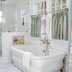 Freestanding Tub Under Window Dressed in Blue Cafe Curtains