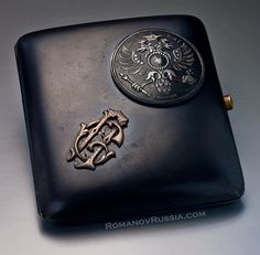 A Highly Important World War I Russian Imperial presentation GUN METAL cigarette case by Carl Faberge. The lid is applied with a round gunmetal medallion a