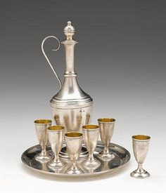 Fine Russian silver vodka set  fabergé, moscow, 1882-99  Matte silver, comprising a decanter with scroll-form handle on stepped circular foot, six beakers with beaded edges and gilt-washed interiors, and a circular tray, 84 zolotnik. (8).  H: 10 1/2 in. (decanter). Dia: 8 in. (tray). Total weight: 22 oz.