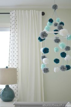 A DIY pom-pom mobile made from yarn and an embroidery hoop is a fun and stimulating addition to your little one's nursery. Find the full tutorial at Pom Pom Baby, Pom Pom Rug, Pom Pom Wreath, Orb Light Fixture, Diy Décoration, Diy Crafts, Easy Diy, Pom Pom Mobile, Mobile Mobile